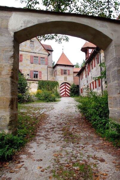 Blick durch das untere Tor auf die Vorburg und den Torturm. Die Grundesburg wurde auf einem Felssporn errichtet, der an ihrem Aufgang sanft ansteigt, an den drei anderen Seiten aber steil abfällt. Foto: Stromerstiftung